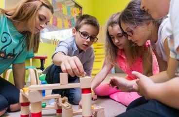 Kinder in Kindergarten mit Erzieherin beim Spielen