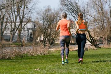 Mutter und erwachsene Tochter joggen als Sport am Fluss entlang