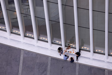 People are seen from a terrace on the 17th floor of 3 World Trade Center as they sit on the exterior of the Oculus in Manhattan, New York