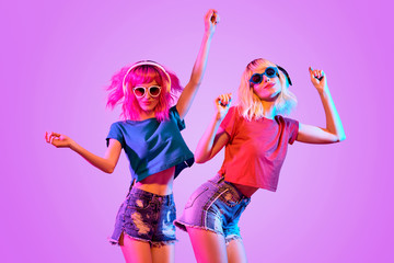 Wall Mural - DJ Girl with Pink Blond Fashion Hairstyle Dance. Two Young Playful Hipster in Trendy Headphones. Sexy Woman in Sunglasses. Music vibrations, Night Clubbing. Creative Art Bright Light