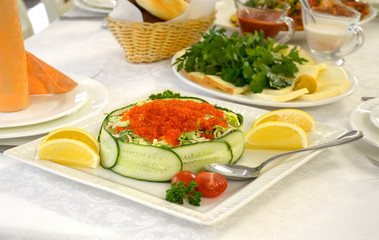 Seafood salad with vegetables and red caviar on the table.