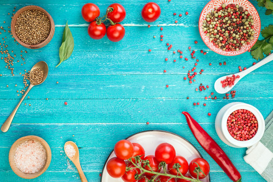 tomatoes on a branch, cherry, turquoise background, red fruits and spices, hot peppers