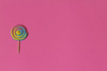 Creative view of colorful, handmade swirl lollipop in summer colors on pink paper background. Minimalism. Abstraction. Creativity.
