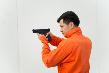 Bandits with gun in hand on white wall background,Thailand people,Prisoner concept