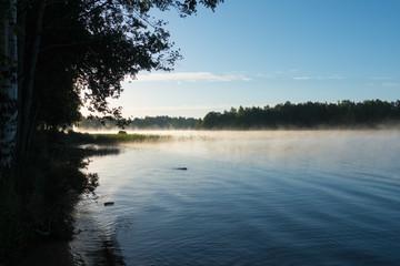 See in Schweden mit Morgennebel im Sommer bei blauem Himmel mit Baumsilhouetten