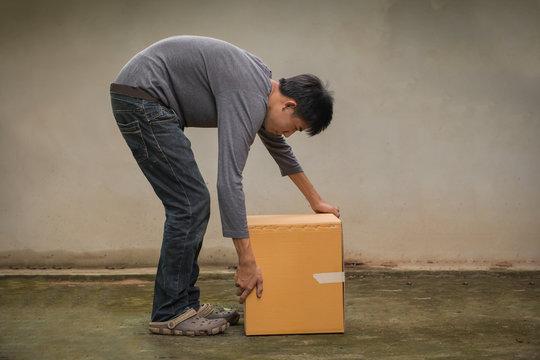 young man bent down, raised cardboard box in an ergonomic posture.
