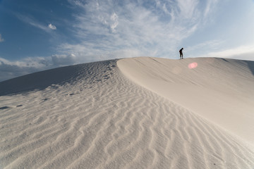 A man walking along a sand dune at White Sands National Monument in Alamogordo, New Mexico.