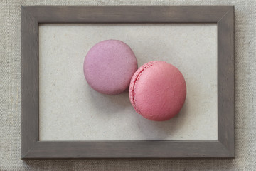 Fresch macaroons of pink and violet colors in wooden frame on wall, unusual abstract sweet art