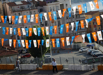 Pedestrians walk under election campaign flags of the AK Party in Istanbul