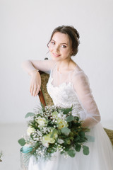 Young beautiful smiling bride with bouquet of flowers sitting in a chair , close-up