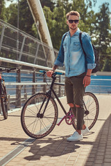 Handsome hipster with a stylish haircut in sunglasses walking with bicycle outdoors.