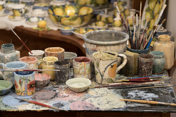 Working desk of a local pianter filled with paint and brushes