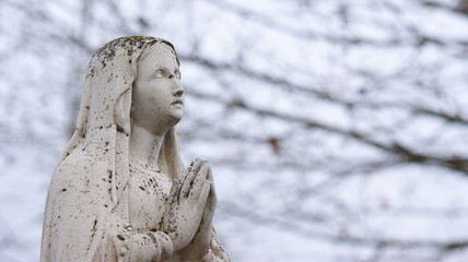 Portrait of a statue of the Virgin Mary with cloudy white sky