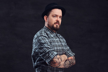 Portrait of a tattoed middle age hipster man with beard and hairstyle dressed in a checkered shirt and hat, pose with crossed arms in a studio.