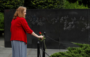 Laura Nelson places a rose at the Korean War Veterans Memorial in Washington