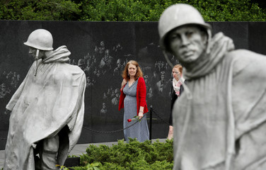 Laura Nelson carries a rose to the Korean War Veterans Memorial in Washington