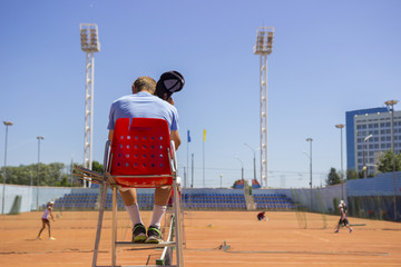Chair umpire (tennis referee) on the position during game. The umpire is hot. Hot refereeing