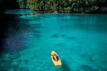 Fotobehang Ontspanning Summer holidays vacation travel. Young woman sailing on paddle board in beautiful calm lagoon.