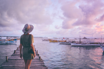 Photography and travel. Young woman in hat holding camera standing on wooden fishing pier with beautiful tropical sea view.