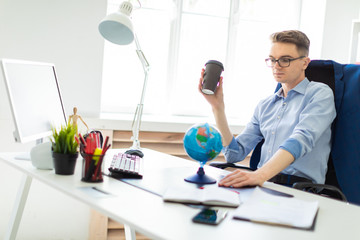 A young man sits in the office at a computer desk and holds a glass of coffee in his hand. A young man faces a globe.