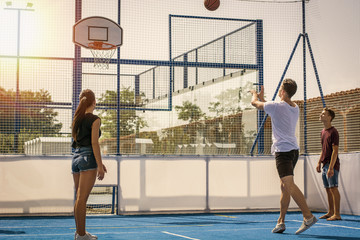 Young handsome men and women wearing shorts playing basketball on playground court