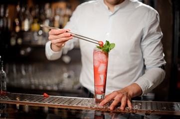 Barman decorating a glass of fresh and sweet strawberry mojito summer cocktail with a berry