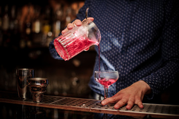 Barman pouring fresh and sweet pink summer cocktail into the glass
