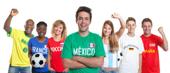 Mexican soccer supporter with crossed arms and fans from other countries
