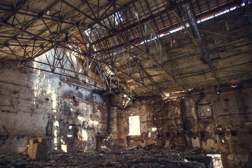 Ruins of abandoned old broken industrial factory or warehouse buildings after disaster, war or cataclysm