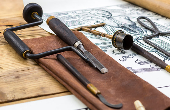 medical instruments medieval surgery drill on a leather cover on background wooden table