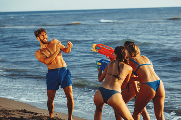 Happy people with water guns have fun on the beach by the sea