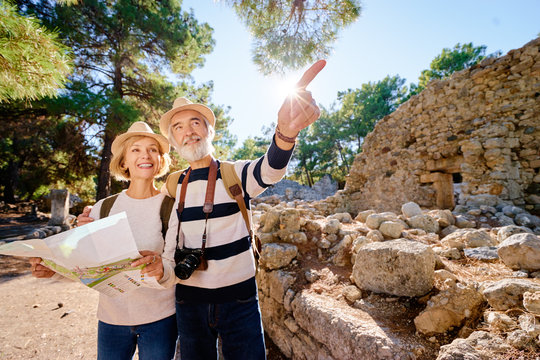 Family, age, tourism and travel concept. Happy senior couple with map at ancient sightseeing.