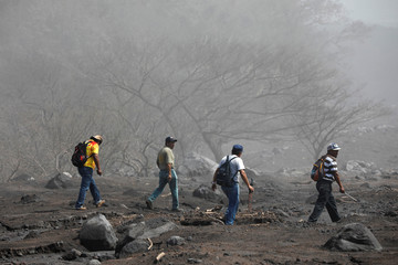 Volunteers are seen amidst ash at an area affected by the eruption of the Fuego volcano at San Miguel Los Lotes in Escuintla
