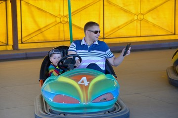 Father and son in amusement park ride on car