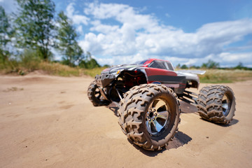 Radio controlled car model in race on the sandy road.