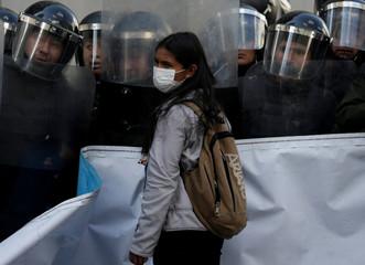 A student from the UPEA (El Alto Public University) stands next to riot policemen in vigil in La Paz