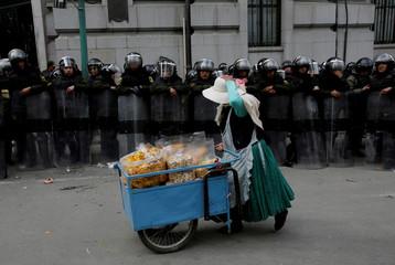 A vendor of snacks walks in front of riot policemen next to Bolivia's vice presidency building in La Paz