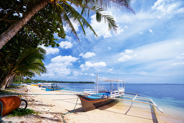 Beautiful landscape with tropical white sand beach with fishing boats. Siargao Island, Philippines.