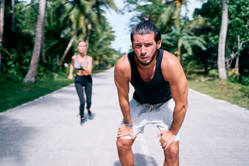 Sport lifestyle. Jogging outdoors. Young couple running under palm trees. Man is tired because of heat.