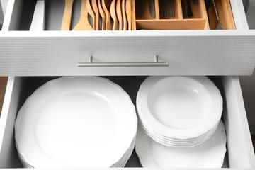 Set of ceramic plates in kitchen drawer, closeup