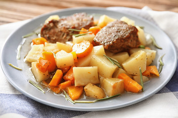 Plate with tasty meat and potatoes on table