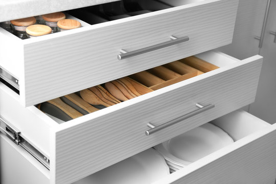 Set of ceramic plates and utensils in kitchen drawers
