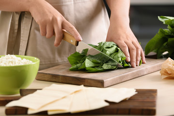 Woman cooking spinach lasagna in kitchen