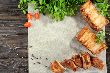 Composition with delicious grilled ribs on wooden table