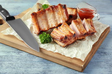 Wooden board with delicious grilled ribs on table