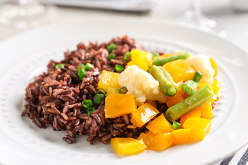 Plate with delicious brown rice and vegetables, closeup