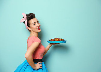 Funny young housewife with homemade pastry on color background