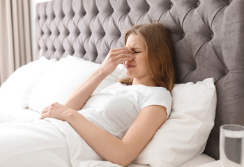 Young woman with terrible headache lying in bed