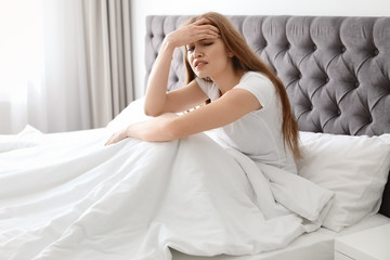Young woman with terrible headache sitting in bed