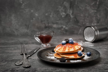 Tasty pancakes with syrup and berries on table